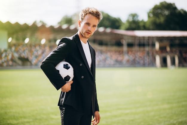 Guapo futbolista en el estadio en traje de negocios