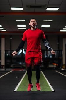 Guapo con grandes músculos saltando sobre una cuerda en el gimnasio.