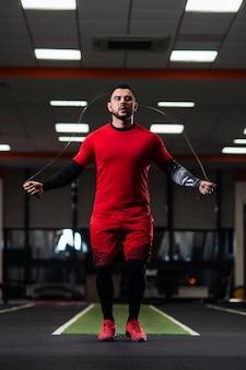 Guapo con grandes músculos saltando sobre una cuerda en el gimnasio