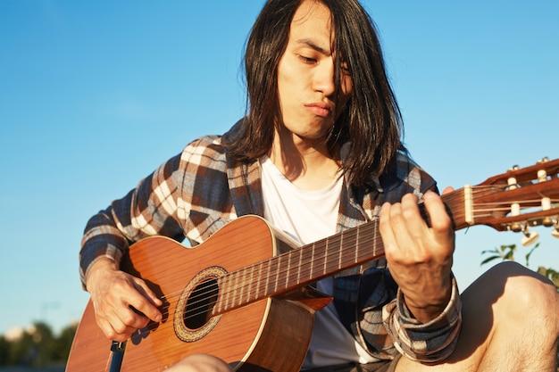 Guapo guitarrista practicando al aire libre