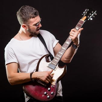 Guapo guitarrista tocando su guitarra eléctrica en pared negra