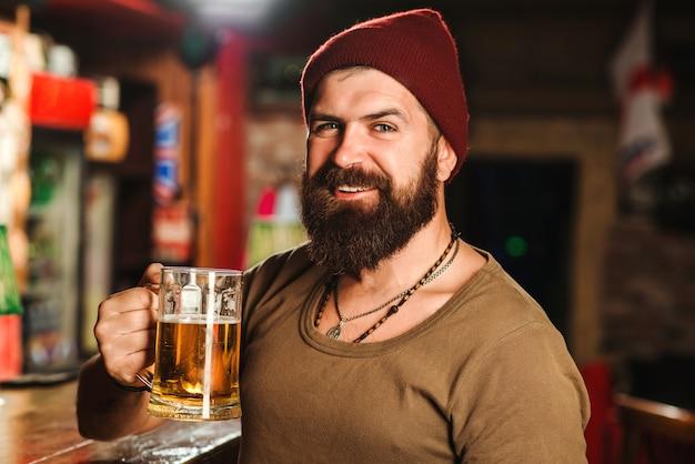 Guapo hipster barbudo sostiene vaso de cerveza
