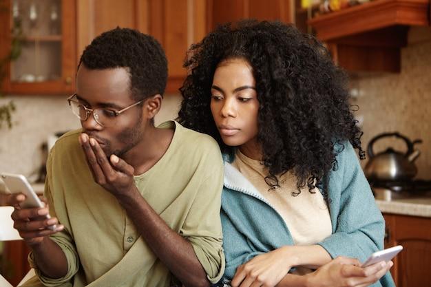 Guapo hombre afroamericano en gafas leyendo sms en el teléfono móvil