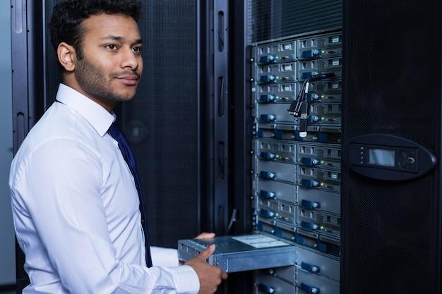 Guapo hombre barbudo encantado de pie cerca del servidor de red e instalando el servidor blade en él mientras hace su trabajo