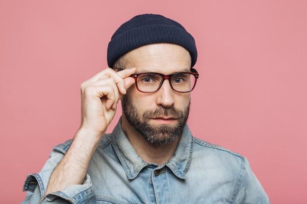 Guapo hombre barbudo con expresión seria usa gafas y anteojos, vestido con camisa de mezclilla de moda