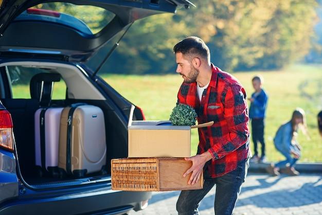 Guapo hombre barbudo de moda carga equipaje en el maletero del coche en un viaje de vacaciones en familia.