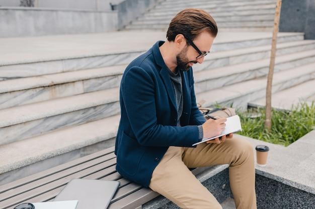 Guapo hombre barbudo sonriente trabajando, escribiendo en el cuaderno