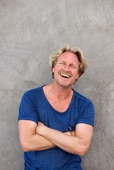 Guapo hombre caucásico sonriendo con los brazos cruzados contra la pared