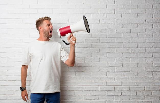 Guapo hombre rubio gritando en un megáfono