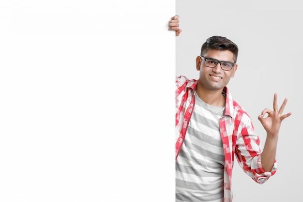 Guapo indio asiático masculino estudiante universitario que muestra el letrero en blanco