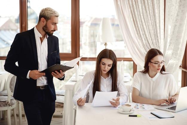 Guapo inspector de restaurante con documentos y dos asistentes femeninas
