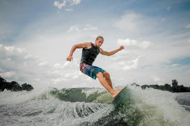 Guapo jinete de wakesurf saltando sobre las olas de un río