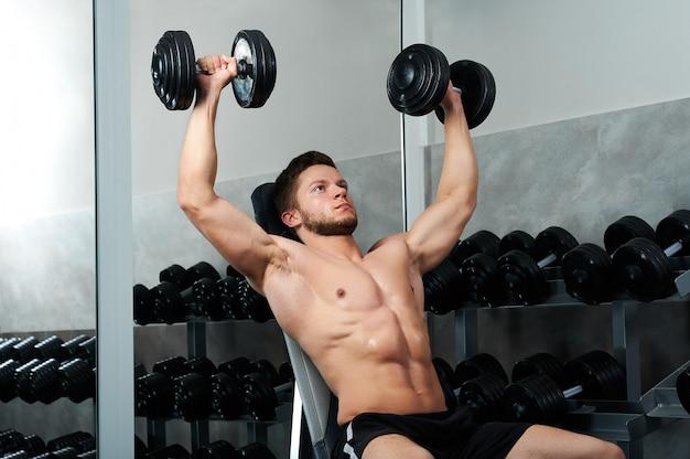 Guapo joven atleta trabajando en el gimnasio