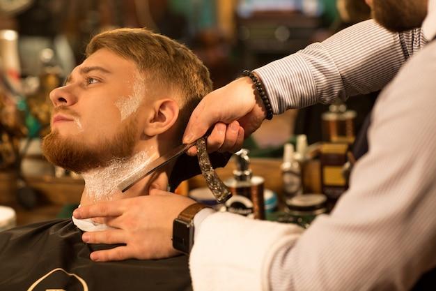 Guapo joven barbudo en la barbería