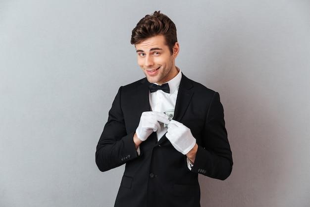Guapo joven camarero mientras mantiene dinero.