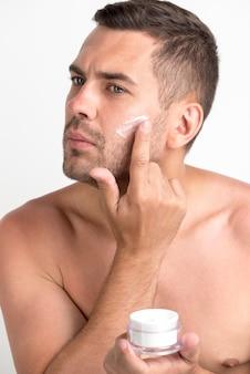 Guapo joven sin camisa cuidando su piel