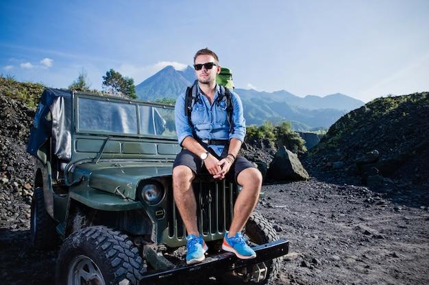 Guapo joven caucásico sentado en el capó de un jeep