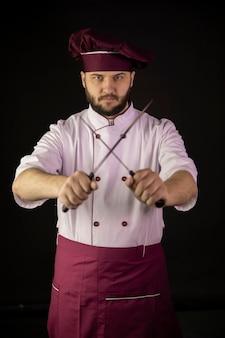 Guapo joven chef masculino barbudo con delantal violeta y gorra sostiene cuchillos afilados cruzados