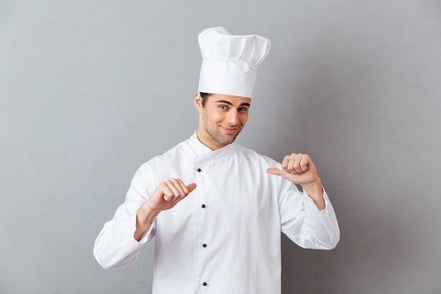 Guapo joven cocinero en uniforme apuntando a sí mismo.