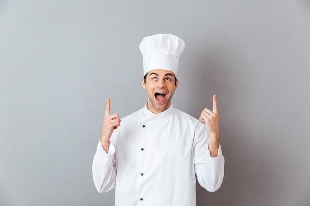 Guapo joven cocinero en uniforme apuntando.