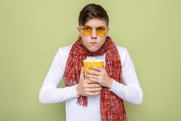 Guapo joven codicioso con bufanda con gafas sosteniendo un cubo de palomitas de maíz aislado en la pared verde oliva