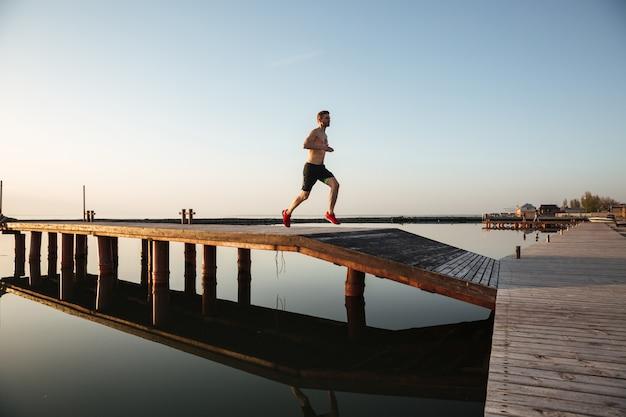Guapo joven deportista corriendo en la playa.
