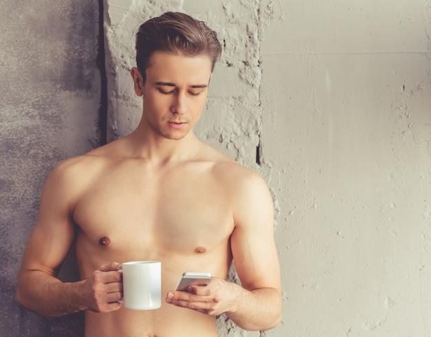 Guapo joven desnudo está utilizando un teléfono inteligente.