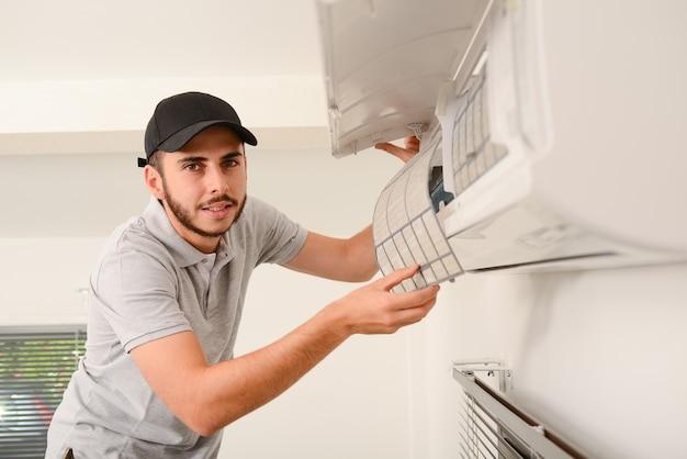 Guapo joven electricista limpiando el filtro de aire en una unidad interior del sistema de aire acondicionado en la casa de un cliente