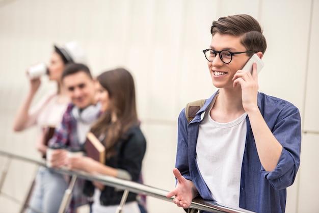 Guapo joven estudiante hablando por teléfono.