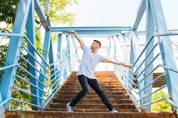 Guapo joven flexible haciendo hip hop en la escalera