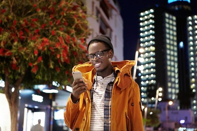 Guapo joven inconformista de piel oscura con sombrero, gafas y mensajes de abrigo de invierno en el teléfono inteligente mientras la espera en la calle por la noche, mirando la pantalla con una sonrisa alegre