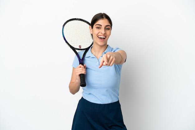Guapo joven jugador de tenis mujer caucásica aislada sobre fondo blanco apuntando al frente con expresión feliz