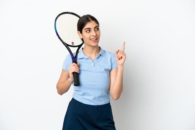 Guapo joven jugador de tenis mujer caucásica aislada sobre fondo blanco apuntando hacia una gran idea