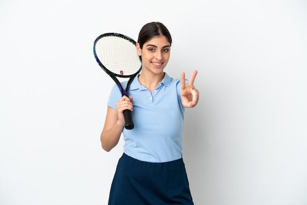 Guapo joven jugador de tenis mujer caucásica aislada sobre fondo blanco sonriendo y mostrando el signo de la victoria
