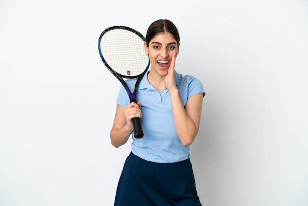 Guapo joven jugador de tenis mujer caucásica aislada sobre fondo blanco con sorpresa y expresión facial conmocionada