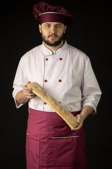 Guapo joven panadero macho barbudo con delantal violeta y gorra sosteniendo pan baguette en las manos