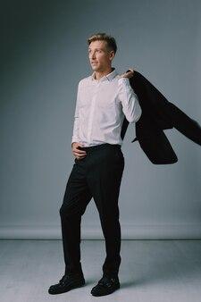 Guapo joven rubia posando con traje elegante