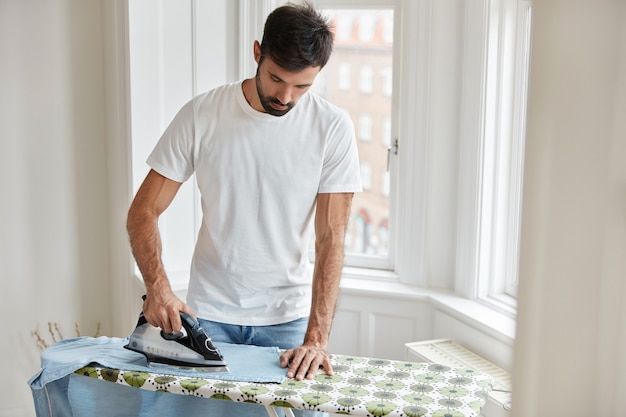 Guapo marido plancha la ropa en la tabla de planchar