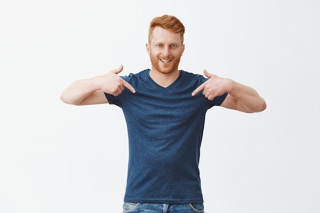 Guapo modelo masculino pelirrojo confiado y orgulloso con cerdas en camiseta azul, apuntando a sí mismo con los dedos índices y sonriendo