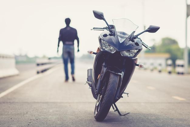 Guapo motorista con casco en manos de moto.