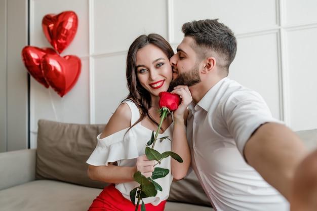 Guapo pareja hombre y mujer haciendo selfie con rosas rojas y globos en forma de corazón en su casa en el sofá