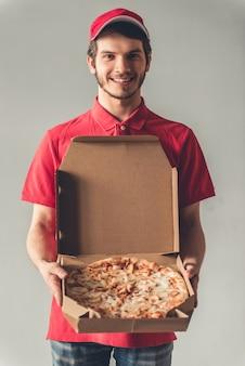 Guapo repartidor en uniforme rojo está sosteniendo una pizza.