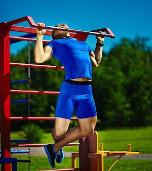 Guapo sano feliz atleta srtong hombre masculino haciendo ejercicio en el parque de la ciudad - conceptos de fitness en un hermoso día de verano en la barra horizontal