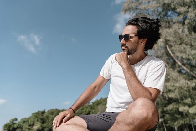 Guapo sexy morena hombre latino con barba en gafas de sol y una camiseta blanca de perfil contra un paisaje tropical
