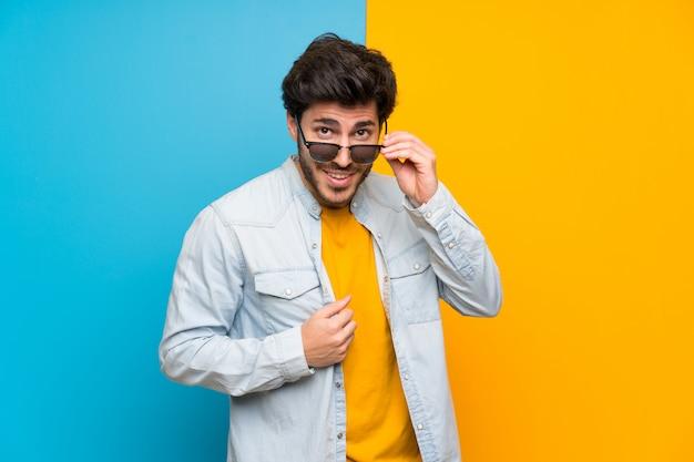Guapo sobre aislado colorido con gafas y sorprendido