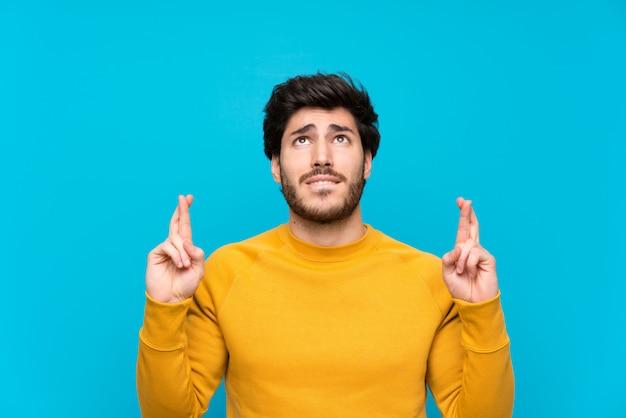 Guapo sobre pared azul aislada con los dedos cruzando y deseando lo mejor