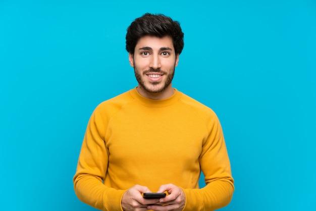 Guapo sobre pared azul aislada enviando un mensaje con el móvil