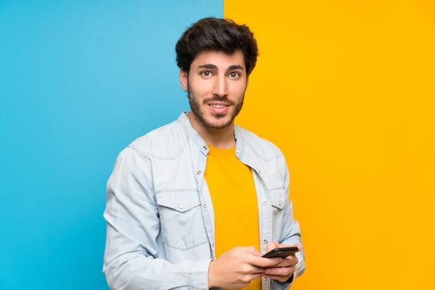 Guapo sobre pared colorida aislada enviando un mensaje con el móvil