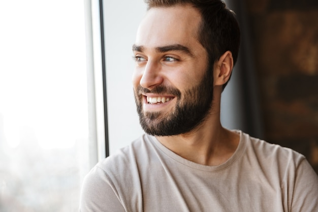 Guapo sonriente joven barbudo de pie junto a la ventana en casa, mirando a otro lado