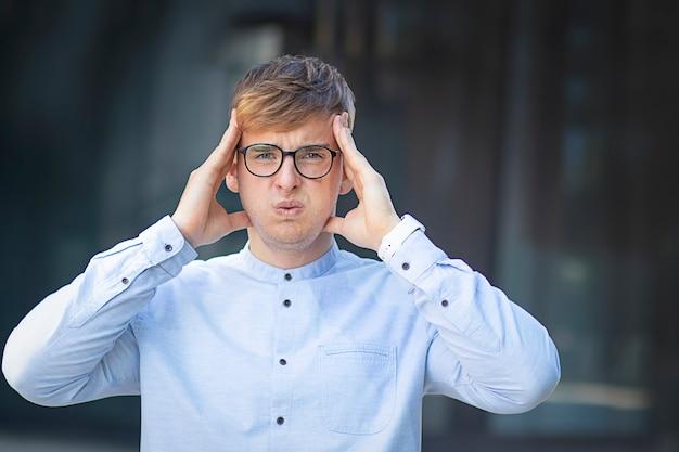 Guapo sosteniendo su cabeza con ambas manos, dolor de cabeza o estrés.